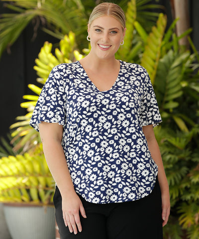 navy and white printed floral top with v-neck and flutter sleeves