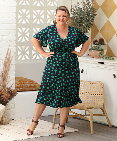 wrap dress with flutter sleeves and skirt ruffle in green and navy polka-dot print