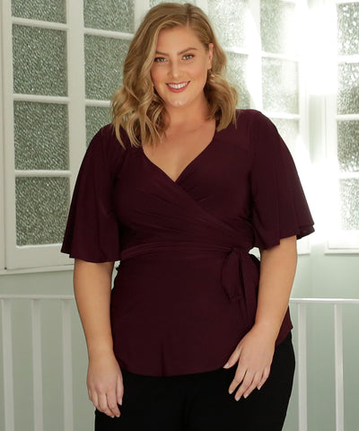mulberry coloured wrap top with full volume flutter sleeves and flattering peplum