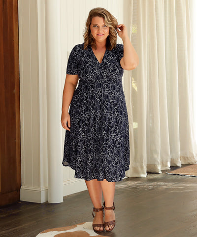 navy and white empire-line dress with twist detail on bodice and dipped hemline