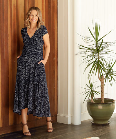 mid-length wrap dress with short sleeves and deep ruffle at hem in navy and white print