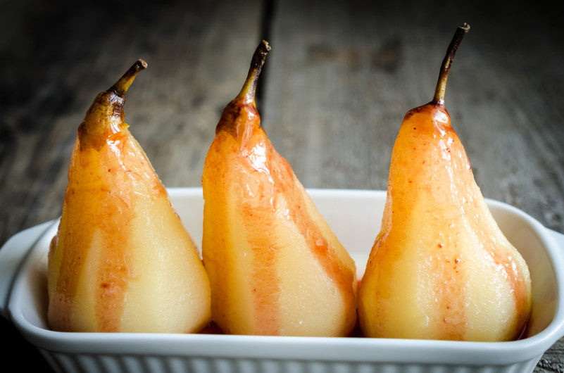 Three poached pears presented in a white serving dish