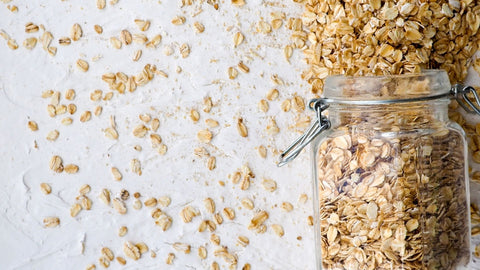 A jar of oats on the right spilled all over on a blank surface.
