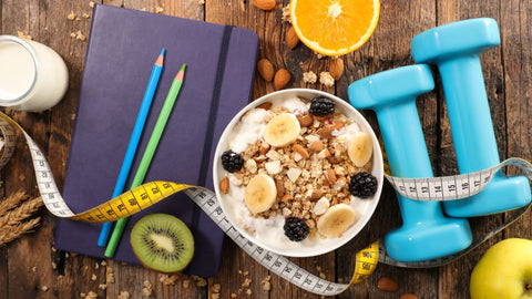 A notebook with pencils on it to the left side, with a bowl of oatmeal in the middle and blue barbells to the left.