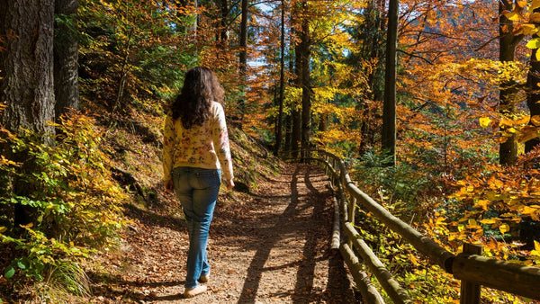 Woman walking on a trail in the woods.