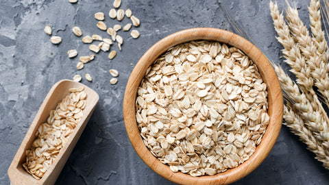 A bowl of oats, with wheat to the right and a spoon of oats to the left.