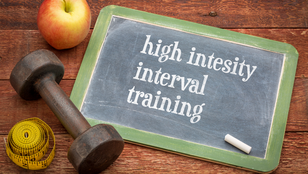 Picture of chalk board with text saying High Intensity Interval Training with healthy snacks and weights next to it
