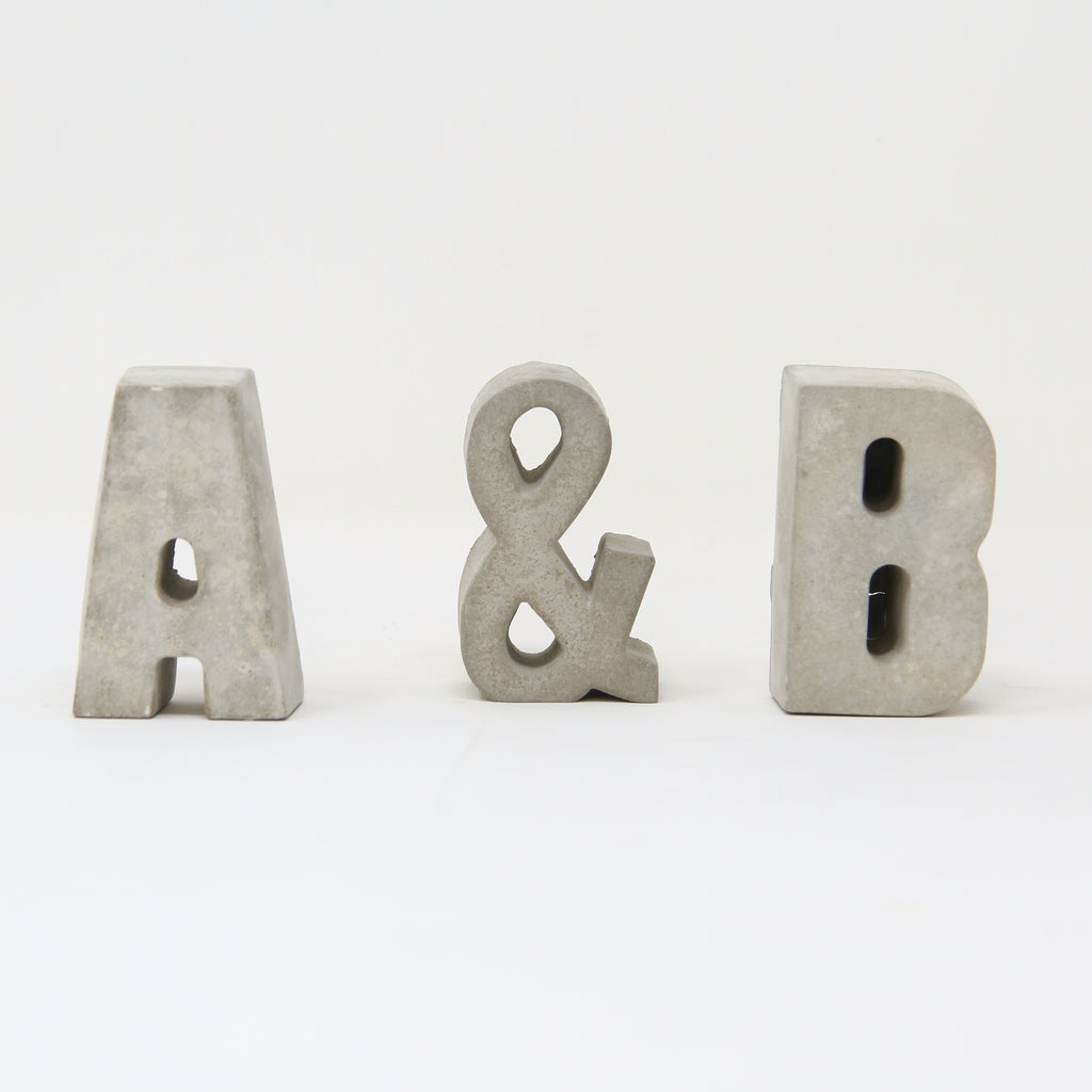 Hand-cast concrete letters with a concrete ampersand by An Artful Life.