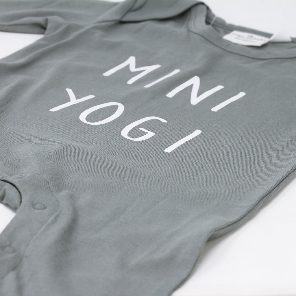 Close up shot of 'Mini Yogi' baby jumpsuit by Yoga Baby.