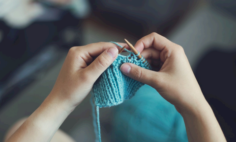 photo of someone knitting with blue yarn