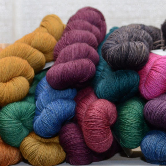 pile of skeined yarn, each in different solid colors