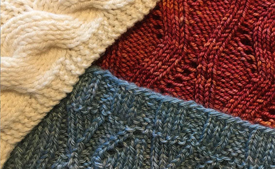 three knitted sample swatches in red yarn, blue yarn, and white yarn