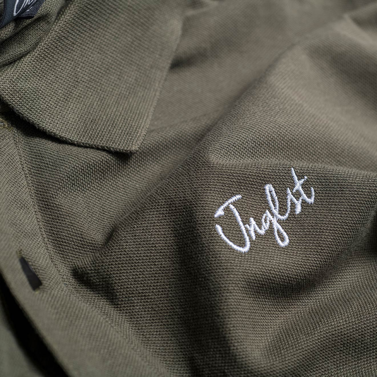 Close up Junglist logo on our Olive Polo Shirt