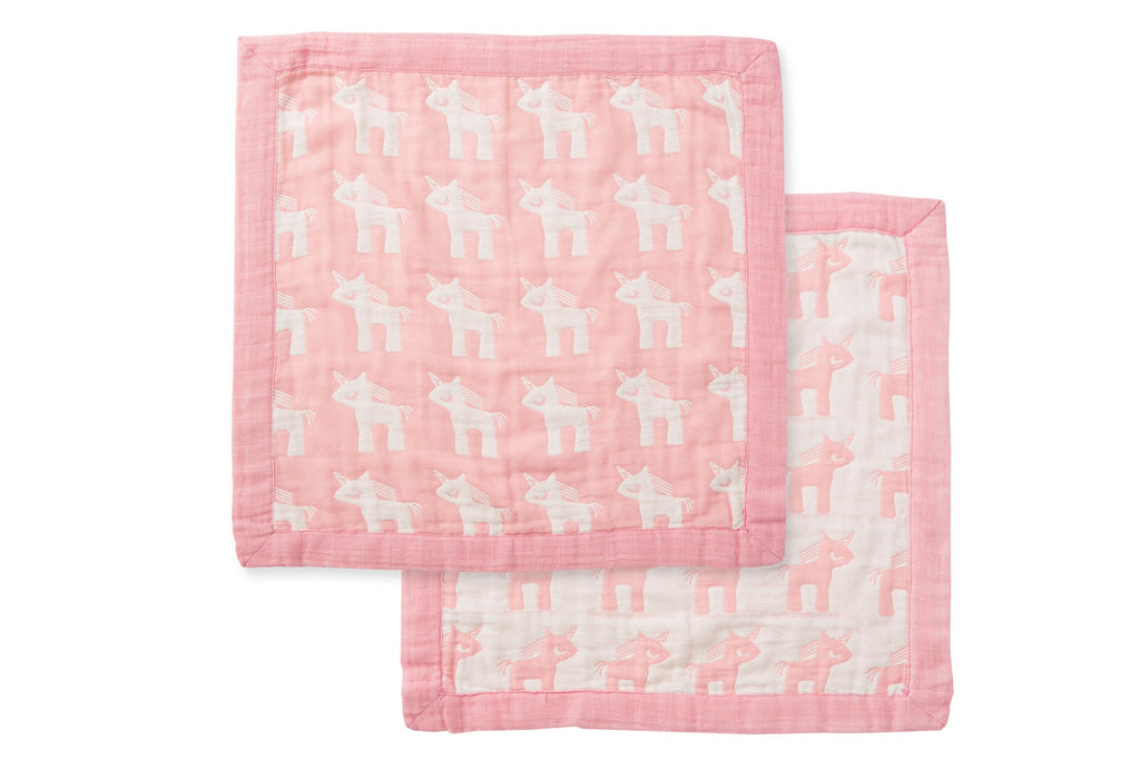 Security blanket covered with white unicorns in front and back with satin pink border around blanket