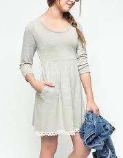 Oatmeal dress on girl with pockets, has a lace/ruffled design at the bottom of the dress, holding a jean jacket and with black sunglasses