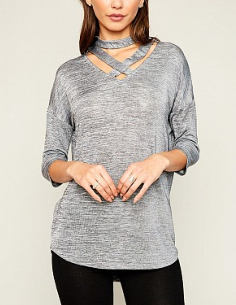 Front of silver tee with cutout choker and cross design sleeves go up to forearms