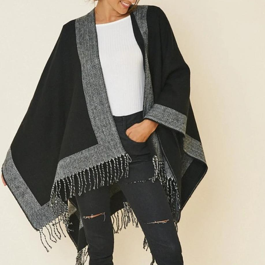 Overall look of poncho, strings hanging around the poncho with a gray border and the rest of the poncho is black