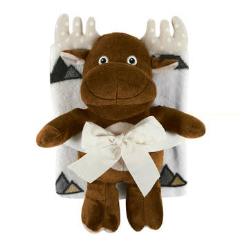 Brown stuffed plush moose and white blanket with mountain figures