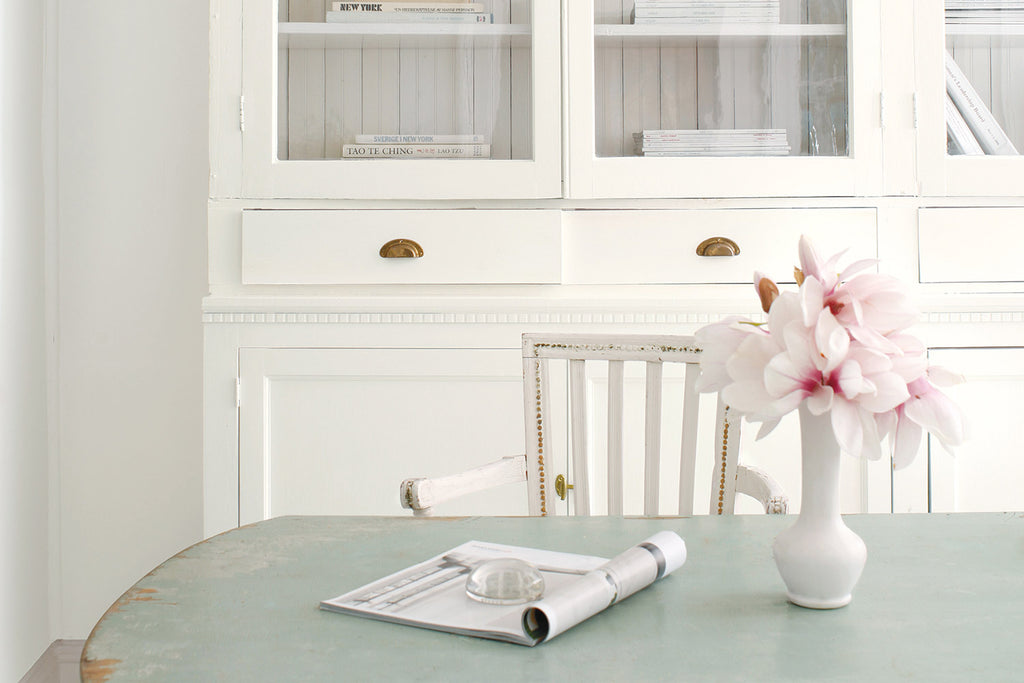 rustic painted dining table with flower vase in front of white painted cabinet