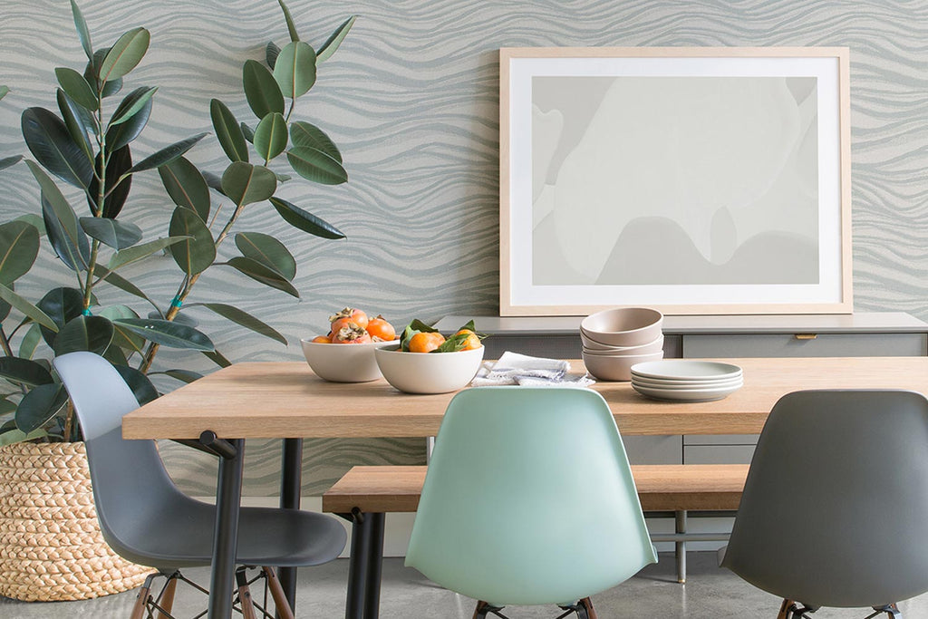 two bowls of fruit on wooden dining table with three different coloured dining chairs in blue wallpapered room