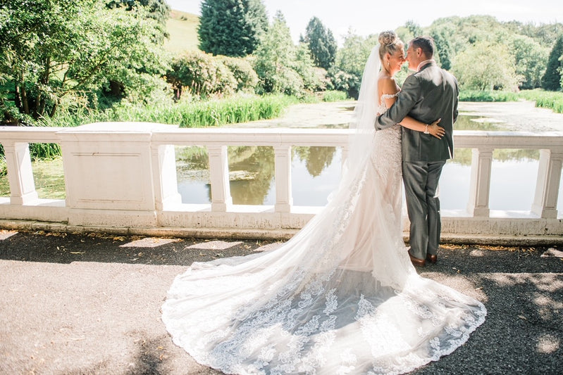 Couple getting married in front of a lake standing on a bridge