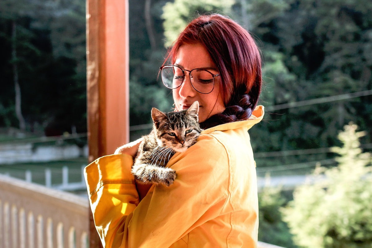 woman wearing yellow jacket holding cat over shoulder