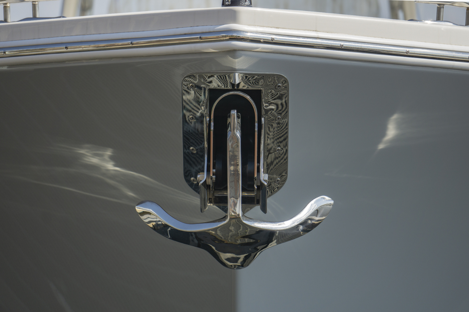 Front close up view of the bow of a boat with a mounted stainless steel anchor