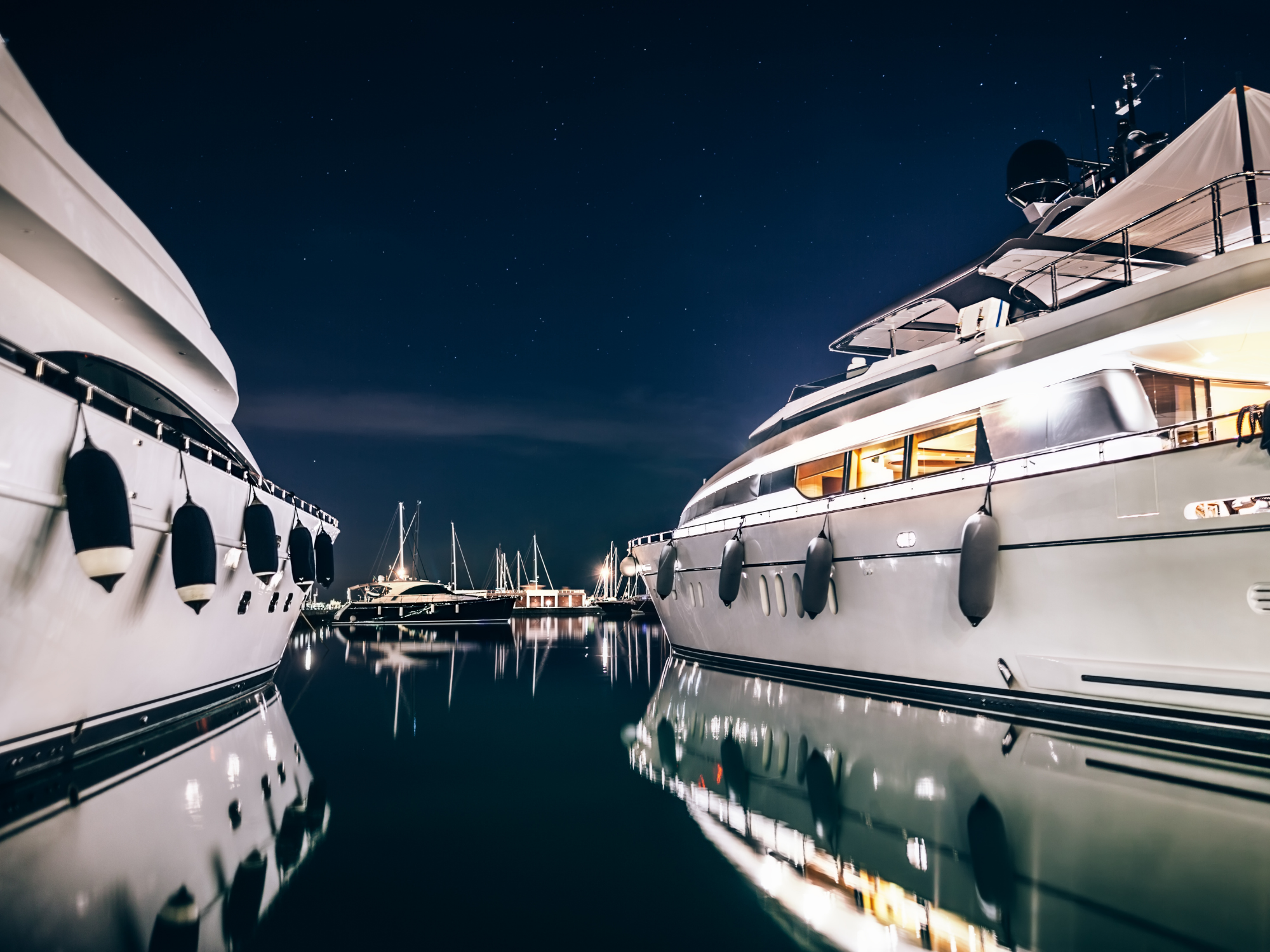 Two large yachts docked side by side with various types of boat lights shown