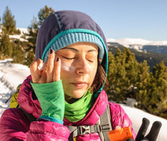 woman in a winter scene applying sunscreen to her face