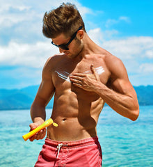 man applying sunscreen to his chest