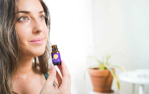 woman holds open bottle of Protector essential oil blend inhaling the aroma