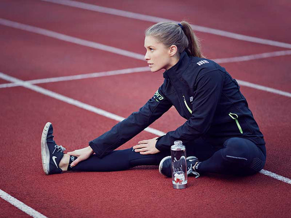 woman stretching on a track with VitaJuwel ViA Crystal Water Bottle