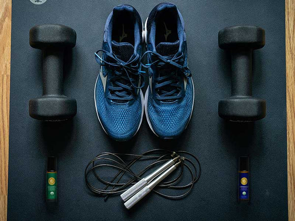 overhead photo, gym knolling: running shoes, barbells, jump rope, peppermint and eucalyptus essential oil roll-ons sitting on a yoga mat