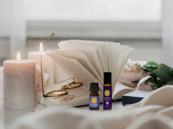 candles, book and glasses on a bedside table with lavender essential oil roll-on and restful ease essentail oil blend bottles