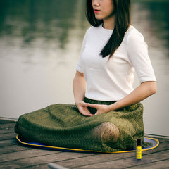 woman meditating with frankincense roll-on next to her