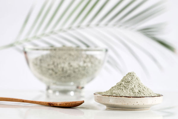 Powdered green clay stacked in a dish with a bowl full in the background, a palm frond in the background and a bamboo spoon rests next to the dishes