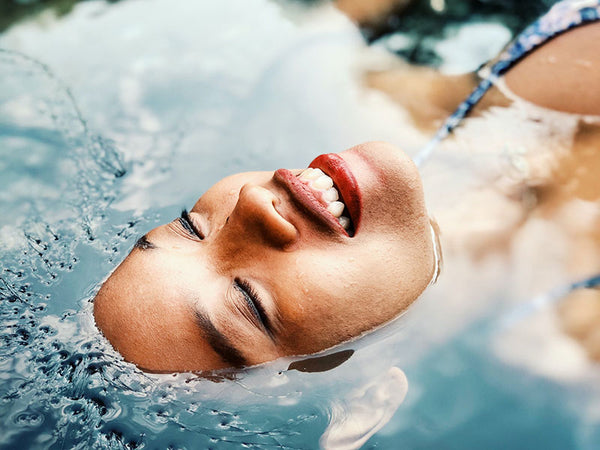 woman laying in water with her face above the water, she is smiling with eyes closed