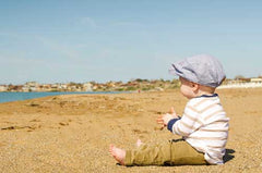 baby in clothing and hat sitting on a sunny beach