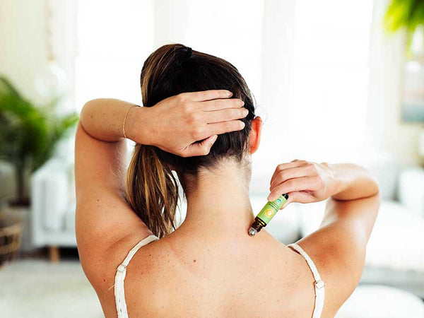 woman applies muscle relief essential oil roll-on to the back of her neck