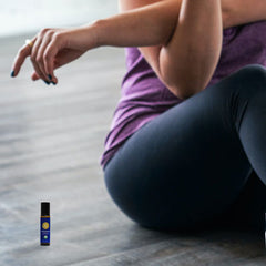 woman sitting on the floor and stretching with peppermint roll-on next to her