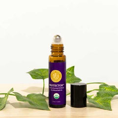protector blend essential oil roll-on with the cap off and sitting a counter with ivy