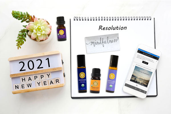 desktop showing calendar 2021 happy new year, mobile phone with meditation audio featured on screen, a succulent, essential oils and notepad that says resolutions: mindfulness