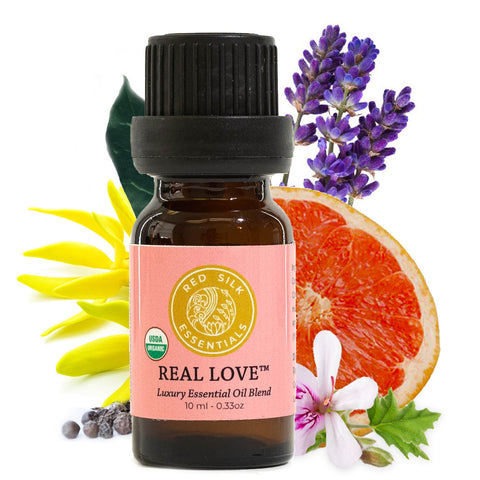 red silk essentials real love blend bottle with botanicals it contains behind it: geranium, pink grapefruit, ylang ylang, black pepper, copaiba balsam and lavender