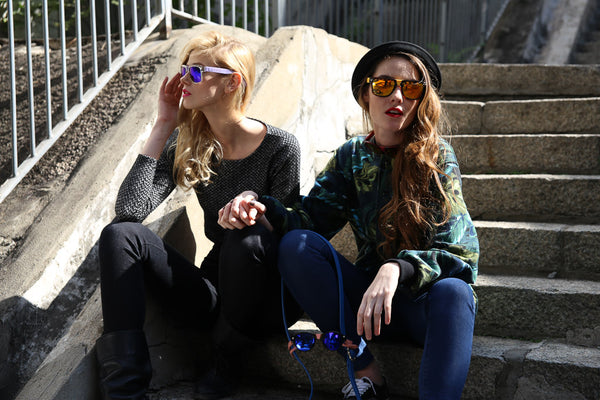 two models sitting wearing sunglasses