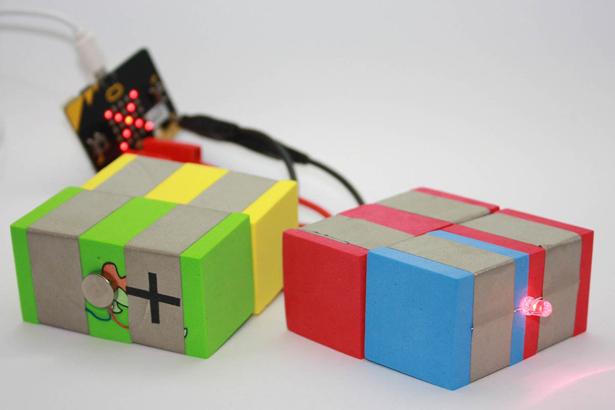 On the left a vibration TapeBlock with a TapeBlock connecting to a cable and banana plug, attached to a Micro:bit and on the right a LED TapeBlock connecting to a cable and banana plug, attached to the same Micro:bit which is in the background