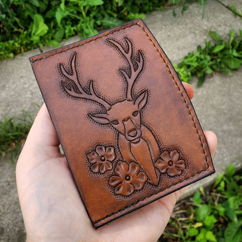 brown minimalist wallet with deer and flowers tooled on it.