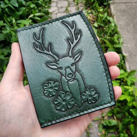 green minimalist wallet with deer and flowers tooled on it.