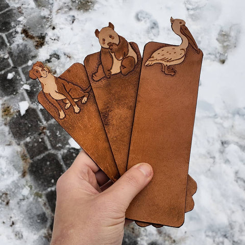 Hand-tooled brown leather boxer dog, panda bear, and pelican bookmarks