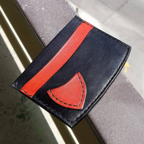 black and orange minimalist card wallet with two card slots and a pick pocket for a guitar pick.