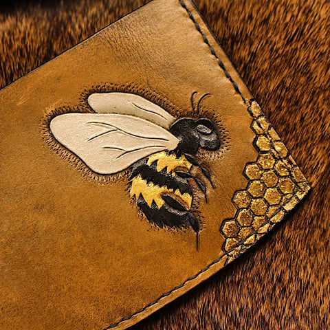 brown minimalist wallet with a bee and honeycomb pattern tooled and stamped on it, and painted with glitter gold, black, and silver paint.